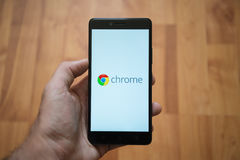 Chrome logo on smartphone screen. London, United Kingdom, june 5, 2017: Man holding smartphone with Chrome logo on the screen. Laminate wood background Stock Image