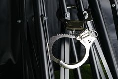 The chrome metal handcuffed bondage on the tripod scene. The chrome metal handcuffed bondage on the tripod black color represent the crime abstract concept Royalty Free Stock Photography