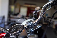 Chrome parts and heated grips on motorbike handlebar Stock Image
