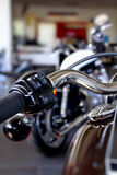 Chrome parts and heated grips on motorbike handlebar Royalty Free Stock Image