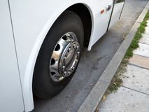 Chrome pläterade hjulet av den vita intercity bussen på streen royaltyfri bild