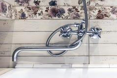 Chrome pläterade vattenkranen i inre av badrummet arkivbilder