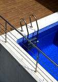 Chrome and pool. A swimming pool on a terrace with a chrome rail and brown tiles royalty free stock images