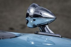 Chrome Racing Mirror on a sports car. A chrome racing rear view mirror mounted on the fender of a blue vintage sports car Stock Images