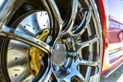 Chrome rims with a background of the red side of a car. Various tires at a southern California event Royalty Free Stock Photos