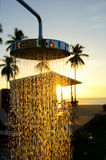 The chrome shower. Next to the swimming pool with silhouette coconut tree and sunrise background stock photo