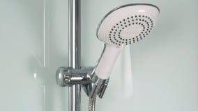 Chrome shower. Bath shower on white tile wall. Shower head  on white shower cabin. 4K Royalty Free Stock Photo