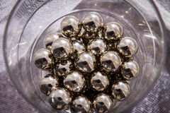 Chrome spheres in clear glass next to the window. Royalty Free Stock Photography