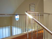 Chrome stairway. Polished wooden floor, and shutters on the top floor of a unit Royalty Free Stock Images