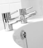 Chrome taps & waste. On white bath Royalty Free Stock Photography