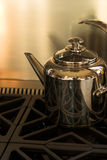 Chrome tea kettle. On stove with stainless steel area blank for text royalty free stock image