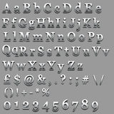 Chrome Text. Letter numbers and symbols in a raised chrome effect on a grey background Royalty Free Stock Photo