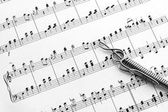 Chrome treble clef on sheet music royalty free stock photography