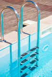 Chrome-Treppe mit leerem Swimmingpool Stockbilder