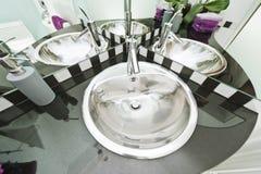 Chrome-Waschbecken, das mehrfache Zeiten widerspiegelt stockbilder