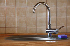 Chrome water faucet in a wooden kitchen Stock Photos