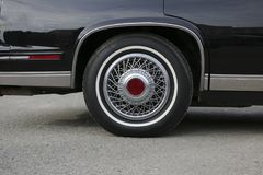 Chrome wheel with silvery spokes and a new rubber on a black shiny Cadillac. Chrome wheel with silvery spokes and  new rubber on  black shiny Cadillac Royalty Free Stock Images