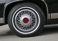 Chrome wheel with silvery spokes and a new rubber on a black shiny Cadillac royalty free stock image