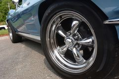 Chrome wheels gleam brightly on a blue sportscar under a sunny early summer day. Five spoked tire stock images