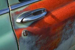 Chrome door handle of a colorful old rusty and semi corroded old car. Chrome, worn paint, and rust on a classic old automobile sitting in an empty lot royalty free stock image