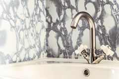 Chromed bright silvery washbasin with white sink. And two valves Royalty Free Stock Photos