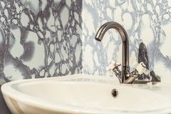 Chromed bright silvery washbasin with white sink. And two valves Stock Photos