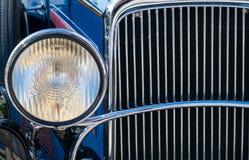Chromed chapeou a luz dianteira e o radiador do carro velho Fotos de Stock
