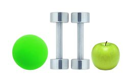 Chromed fitness dumbbells, ball and green apple Royalty Free Stock Photos