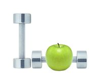 Chromed fitness dumbbells and green apple Royalty Free Stock Image
