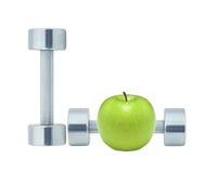 Chromed fitness dumbbells and green apple Royalty Free Stock Image