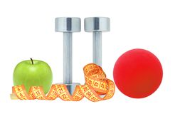 Chromed fitness dumbbells, measure tape red ball and green apple Royalty Free Stock Photography