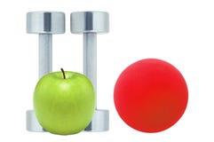 Chromed fitness dumbbells, red ball and apple Stock Photo