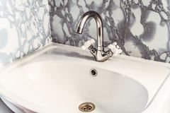 Chromed silvery washbasin with bright white sink. And two valves Stock Photos