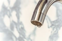 Chromed spout of a water tap with a drop on the aerator. Close-up Stock Images