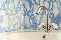 Chromed washbasin with white sink. And two valves Stock Image