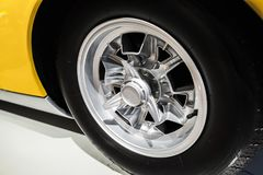 Chromed wheel disc. Yellow vintage sport car. Chromed wheel disc. Yellow luxury Italian vintage sport car fragment, close up photo with selective soft focus Royalty Free Stock Photo