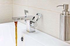 Chromium-plate tap with rusty, dirty  water. Royalty Free Stock Photos