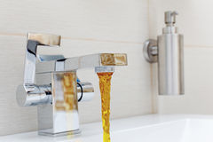 Chromium-plate tap with rusty, dirty  water. Stock Photos