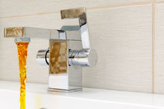 Chromium-plate tap with rusty, dirty  water. Royalty Free Stock Images