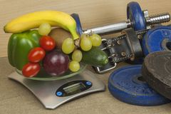 Chromuje dumbbells otaczających z zdrowymi owoc i warzywo na stole Pojęcie zdrowa łasowania i ciężaru strata Zdjęcie Royalty Free
