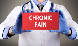 Chronic pain. Doctor`s hands in blue gloves shows the word chronic pain. Medical concept stock photo