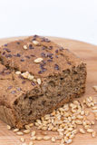 Chrono bread on a wooden board with grains of wheat.  Stock Image