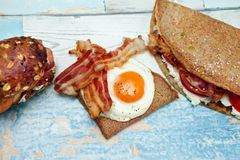 Chrono breakfast - diet concept. Chrono breakfast,  fried egg and bacon on pancakes with stuffed pancake and bun on the table Stock Photos
