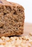 Chrono Brot auf einem hölzernen Brett mit Körnern des Weizens Lizenzfreies Stockbild