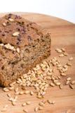 Chrono Brot auf einem hölzernen Brett mit Körnern des Weizens Lizenzfreie Stockfotografie
