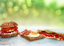Chrono nutrition concept. Pancake breakfast with fried eggs, bacon and stuffed buns on the table, chrono diet concept Stock Images