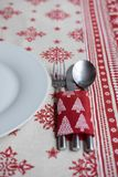 Chrsitmas dinner decoration for table. Christmas table decorated with a glass and a dish over a xmas tablecloth Royalty Free Stock Photo