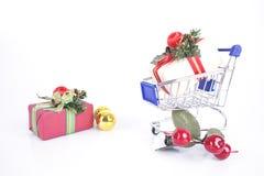 Chrstmas gåvor och shoppingvagn med garnering på en vit tillbaka arkivbilder