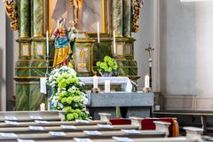 Chruch interior with candles and flowers. Chruch interior with altar and candles and flowers in sun light royalty free stock photography