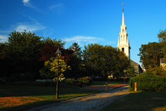 A chruch steeple rises over a public park. The Historic Trinity Church in Newport, Rhode Island stands above a small park in the downtown area Royalty Free Stock Images